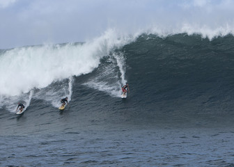 """Three surfers catch a large wave at the surf spot on the outer reefs known as """"Himalayas"""" on the North Shore of Oahu in Haleiwa, Hawaii."""