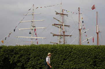 A man passes by tall ships moored on the bank of the River Thames at Woolwich in east London