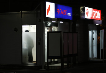 A man is seen inside booths of automated cash dispensers set up by consumer lenders Promise and Acom Co. in Saitama