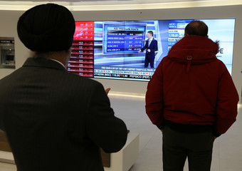 Passersby watch the performance of stocks on a financial news television screen in the business district of Toronto