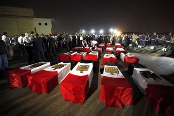 The caskets of 25 policemen killed near the north Sinai town of Rafah lay on the ground after arriving in Cairo
