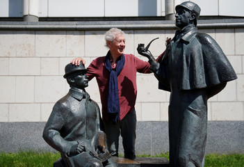 British actor McKellen poses for picture near a statue of writer Arthur Conan Doyle's characters Holmes and Watson in front of British Embassy in Moscow