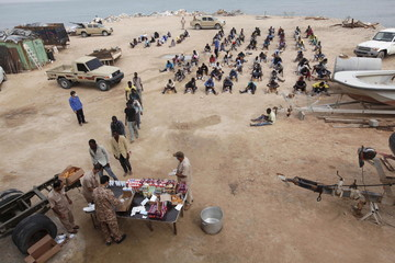 Migrants receive food after they were detained at the coastguard center, in the coastal city of Tripoli