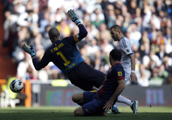 Real Madrid's Benzema scores past Barcelona's goalkeeper Valdes and Mascherano during their Spanish first division soccer match in Madrid