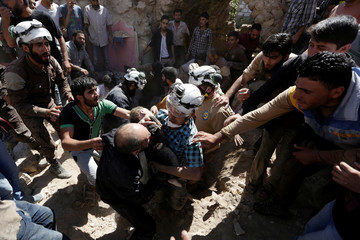 Civil defence members carry the body of a dead child at a site hit by airstrike in the rebel-controlled area of Maaret al-Numan town in Idlib province