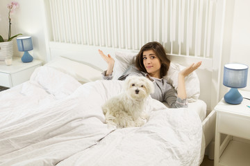Cute woman in bed with siamese dog