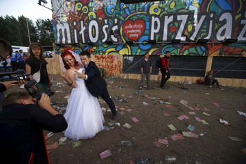 A newly married couple poses during a photo session near the main stage at the 21st Woodstock Festival in Kostrzyn-upon-Odra