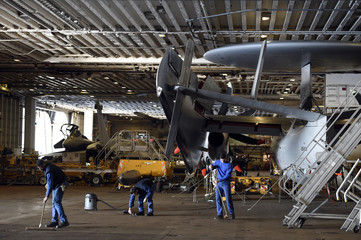 Crew members clean a hangar near a Hawkeye aboard the Charles-de-Gaulle aircraft carrier operating in the eastern Mediterranean Sea