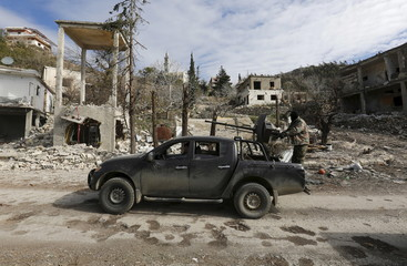 Forces loyal to Assad drive a vehicle mounted with an anti-aircraft weapon in the town of Rabiya