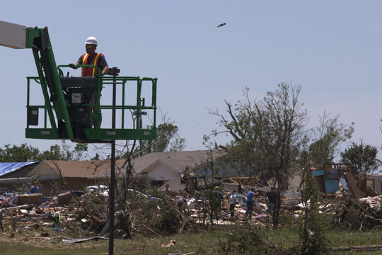 A man on a lift prepares to board up a damaged building as residents in the background go through their belongings after the Oklahoma City suburb of Moore, Oklahoma which was left devastated by a tornado