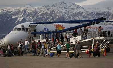 Passengers disembark from a McDonnell Douglas MD-80 series jet belonging to Allegiant Air at the Ogden-Hinckley Airport