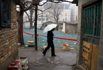 """A security guard carries an umbrella as he walks past what remains of dwellings marked for demolition in an alleyway area, known in Chinese as a """"hutong"""", in central Beijing"""