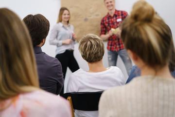 männer und frauen hören einem vortrag zu