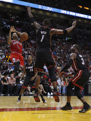 Chicago Bulls Derrick Rose is blocked by the Miami Heat's Chris Bosh as the Heat's Mario Chalmers and Dwyane Wade look on during third quarter NBA basketball action in Miami