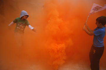 Boys play with a smoke canister during a demonstration by firefighters, security and military personnel against cuts in their salaries imposed by Spanish Government, in Seville