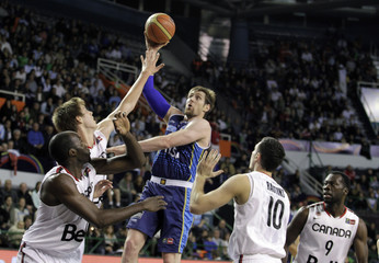 Argentina's Nocioni goes to the basket under pressure from Canada players during their quarter-final FIBA Americas Championship basketball game