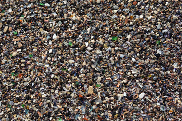 Fragments of glass intermixed with sand. Texture of colored stones