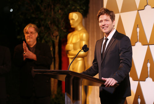 Director Vinterberg accepts his nomination certificate from cartoonist Matt Groening (rear L) at the 86th Academy Awards Foreign Language Nominee Reception at Ray's and Stark Bar on the LACMA Campus in Los Angeles