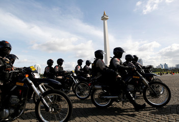 Indonesian police depart on motorcyles following a security briefing at the National Monument before deployment during the Christmas and New Year holidays in Jakarta, Indonesia