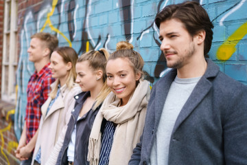 studenten stehen zusammen draußen an einer mauer mit graffiti