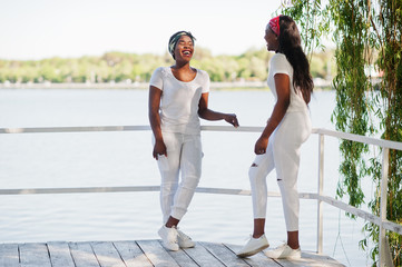 Two stylish and trendy african american girls, wear on white clothes against lake. Street fashion of young black people.