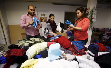 Volunteers sort through clothing donations for Syrian refugees who are expected to arrive in Canada within the next month, at the Middle Eastern Friendship Centre in Surrey