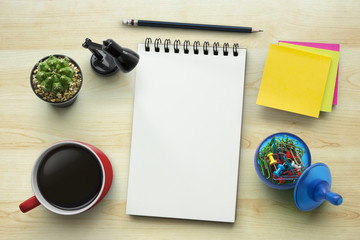 Notebook on office table with a cup of coffee, plant, stationery and office supplies. Blank notepad paper for input copy or text. Top view desk, flat lay wood background concept.