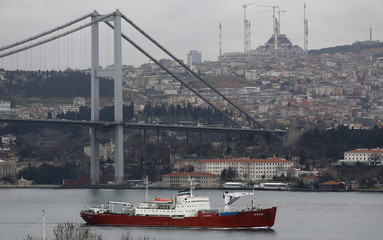 The Russian Navy's transport ship Yauza, with the Bosphorus bridge in the background, sets sail in the Bosphorus, on its way to the Mediterranean Sea, in Istanbul