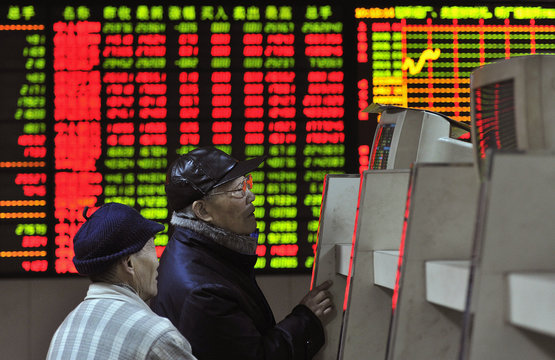 Investors look at a computer screen showing stock information at a brokerage house in Hefei