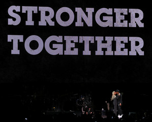 Jay Z and Beyonce share a kiss before Democratic U.S. presidential candidate Hillary Clinton speaks during a free campaign concert in Cleveland