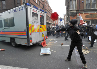 Demonstrators throw traffic cones at a police van, during a protest organised by the Trades Union Congress in central London