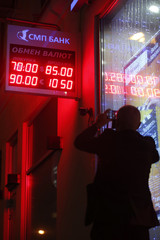 A man takes a picture of a board showing currency exchange rates in Moscow
