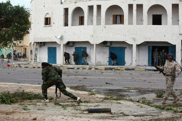 Anti-Gaddafi fighters run for cover during clashes with Gaddafi forces in Sirte