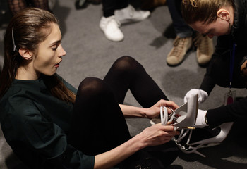A model receives help with her shoes backstage before the Diesel Black Gold Autumn/Winter 2013 collection runway show during New York Fashion Week