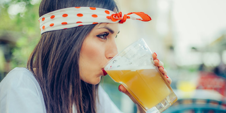 Beautiful young woman drinking beer and enjoying summer day