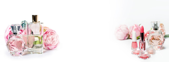 Perfume bottles with flowers on light background. Perfumery, cosmetics, fragrance collection. Free space for text. Banner for website.
