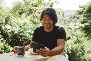 Smiling man using tablet computer while having breakfast in yard