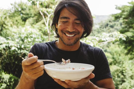 Smiling man having breakfast in yard