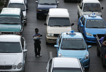 An Indonesian street vendor stands between cars during a traffic jam in Jakarta