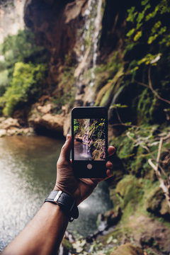 Hiker taking picture of waterfall through smartphone