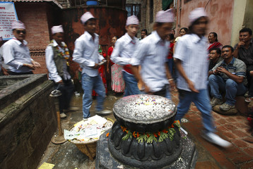 Devotees walk past a stone symbol of a lotus flower during the Mataya festival in Patan