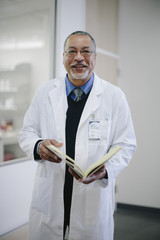 Portrait of smiling male doctor with book standing in hospital