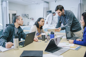 Male doctor discussing with coworkers over tablet computer in medical room