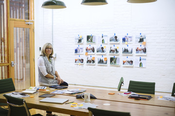 Portrait of businesswoman sitting on table in meeting room