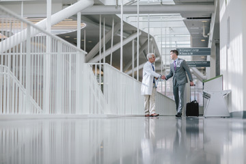 Male doctors shaking hands while walking in hospital corridor