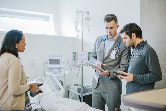 Male doctor training coworkers over tablet computer in medical school