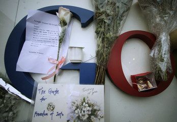 A card, a letter and flowers a are placed on the Google logo at its China headquarters building in Beijing