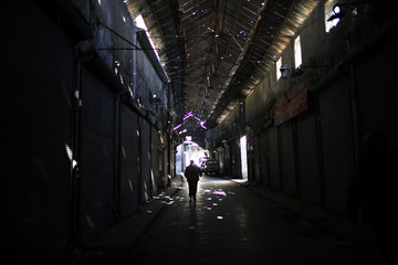 A Free Syrian Army fighter walks inside the market of the old city of Aleppo