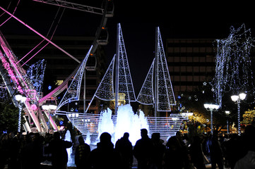 People make their way next to an illuminated boat, traditional Greek symbol for Christmas, on central Syntagma square in Athens, Greece