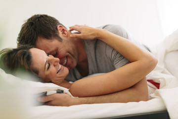 Smiling couple in bed at home